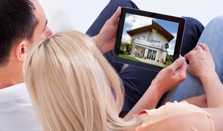 Couple Looking at House for Sale On Ipad