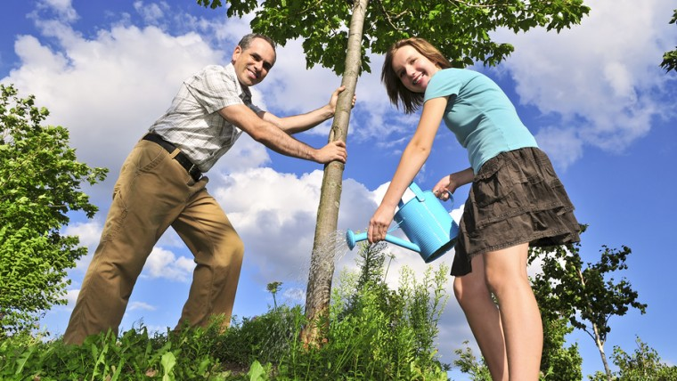Father and daughter watering a young tree