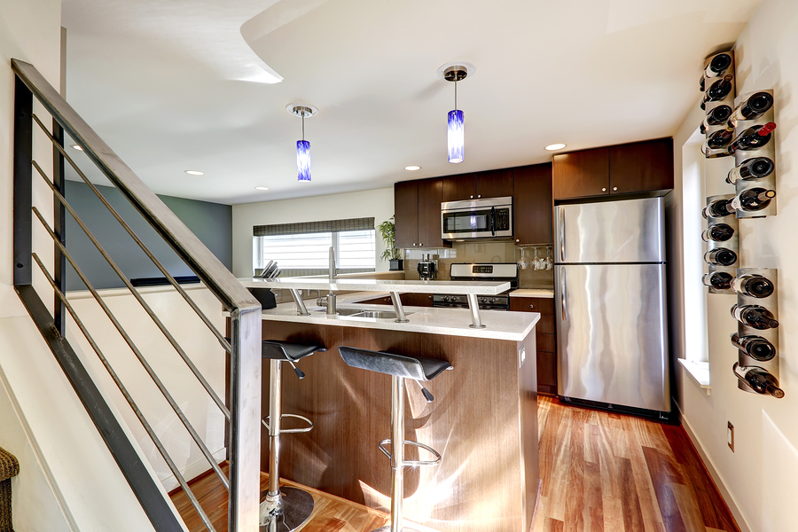Image of small kitchen in a modern apartment. View of steel refrigerator bar with stools and wine racks