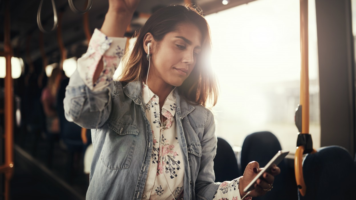 Young woman smiling while riding on a bus listening to music on a smartphone