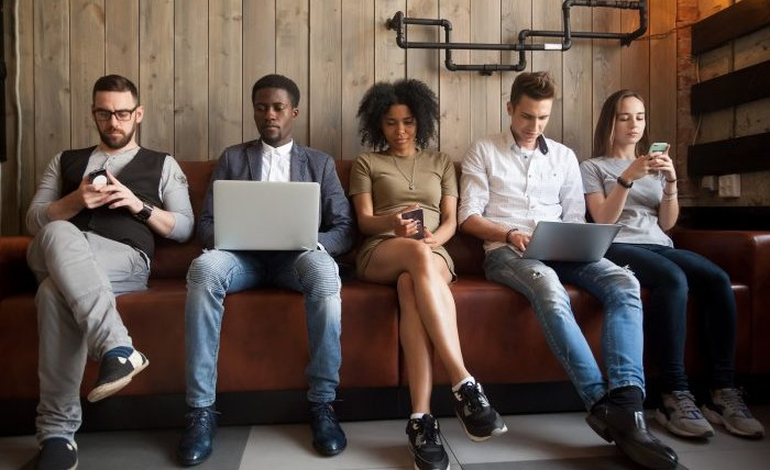 Diverse young people sitting in row on couch together while checking their phones and laptops.