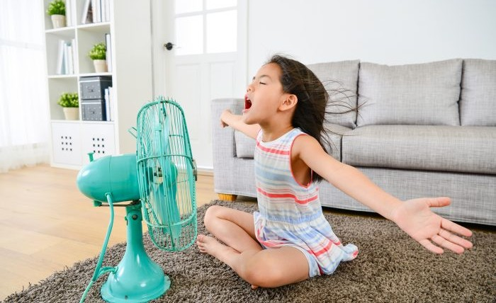A little girl sits in front of a mint colored fan with her arms outstretched.