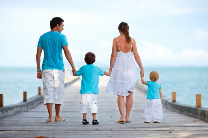 Family of four on wooden jetty by the ocean.