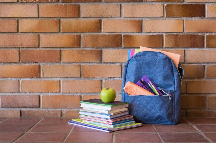 Blue backpack with school supplies against brick wall.