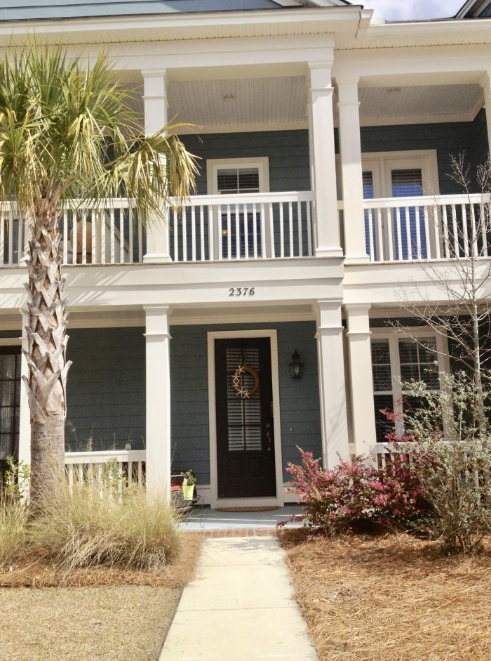 A large, blue, multi-story Charleston home with a Palmetto tree in the yard.