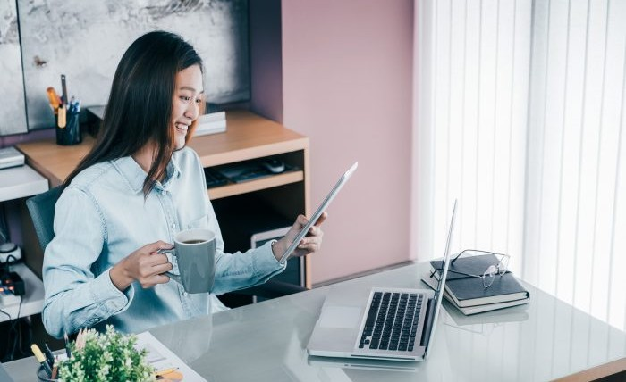 Asian businesswoman takes a coffee break after working at laptop computer on desk with smiling face.
