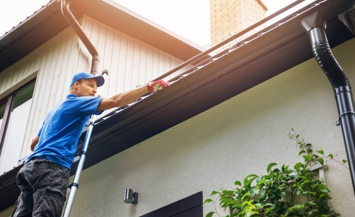 Man on ladder cleaning house gutter from leaves and dirt.