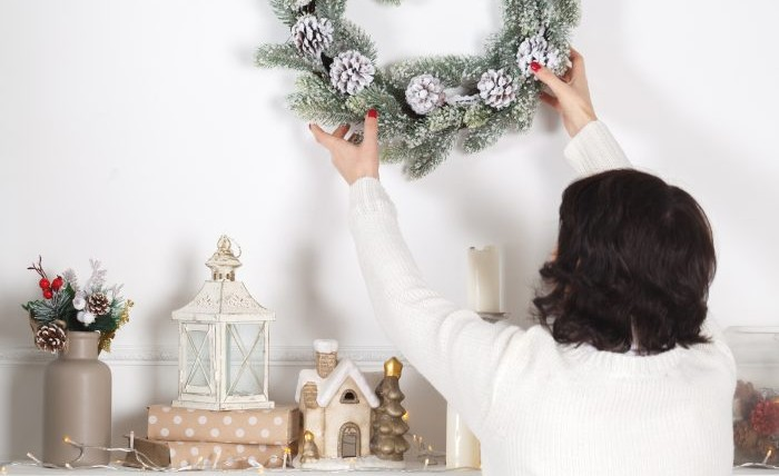 Woman removing wreath from a wall.