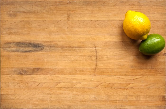A lemon and a lime sit in the corner of a worn cutting board