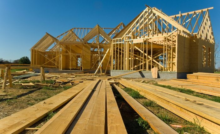 New home under construction with wood trusses and supplies against blue sky.