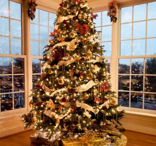 Christmas tree with presents and lights reflecting in windows around the tree in modern home.