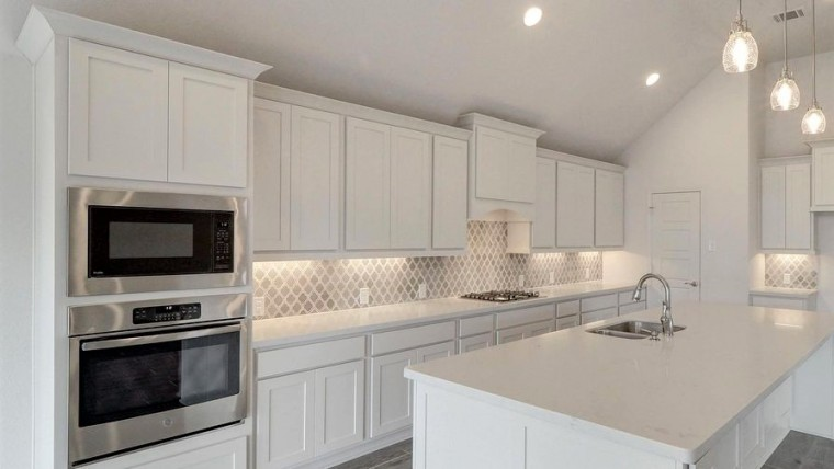 beautiful new, white kitchen with gray accents and tiled backsplash