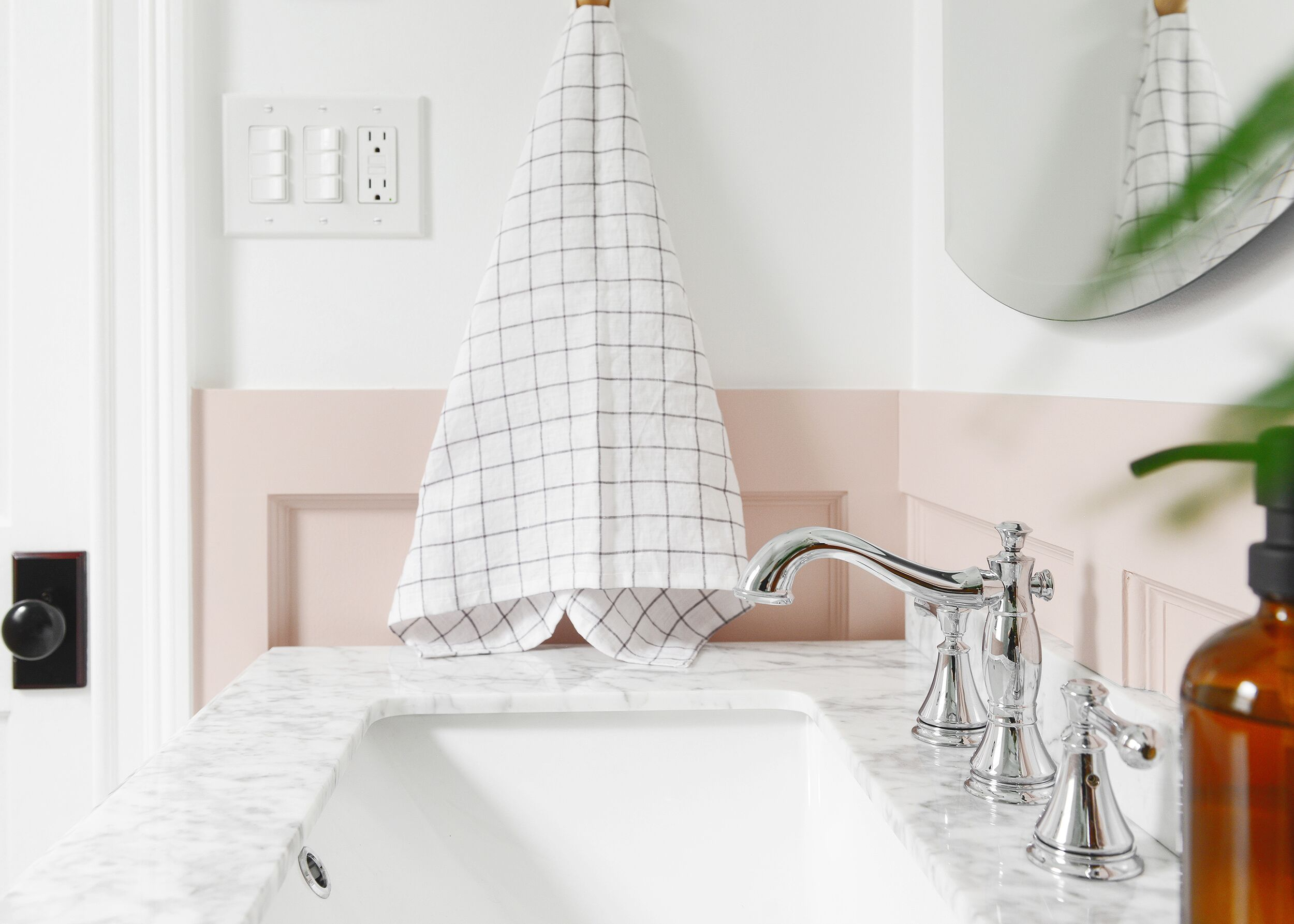 Hand towel with grid pattern hanging in the bathroom adjacent to the mirror
