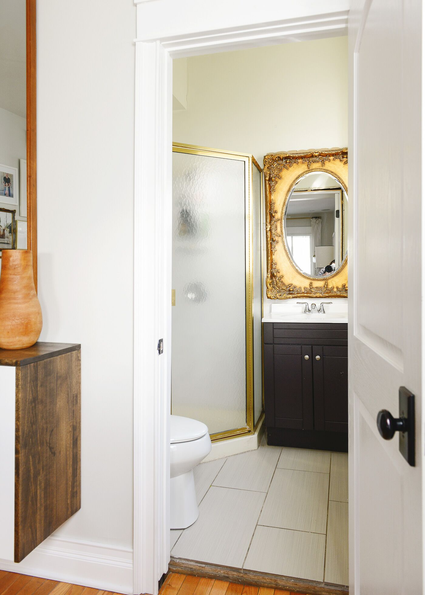 Recently renovated bathroom with gold vintage mirror