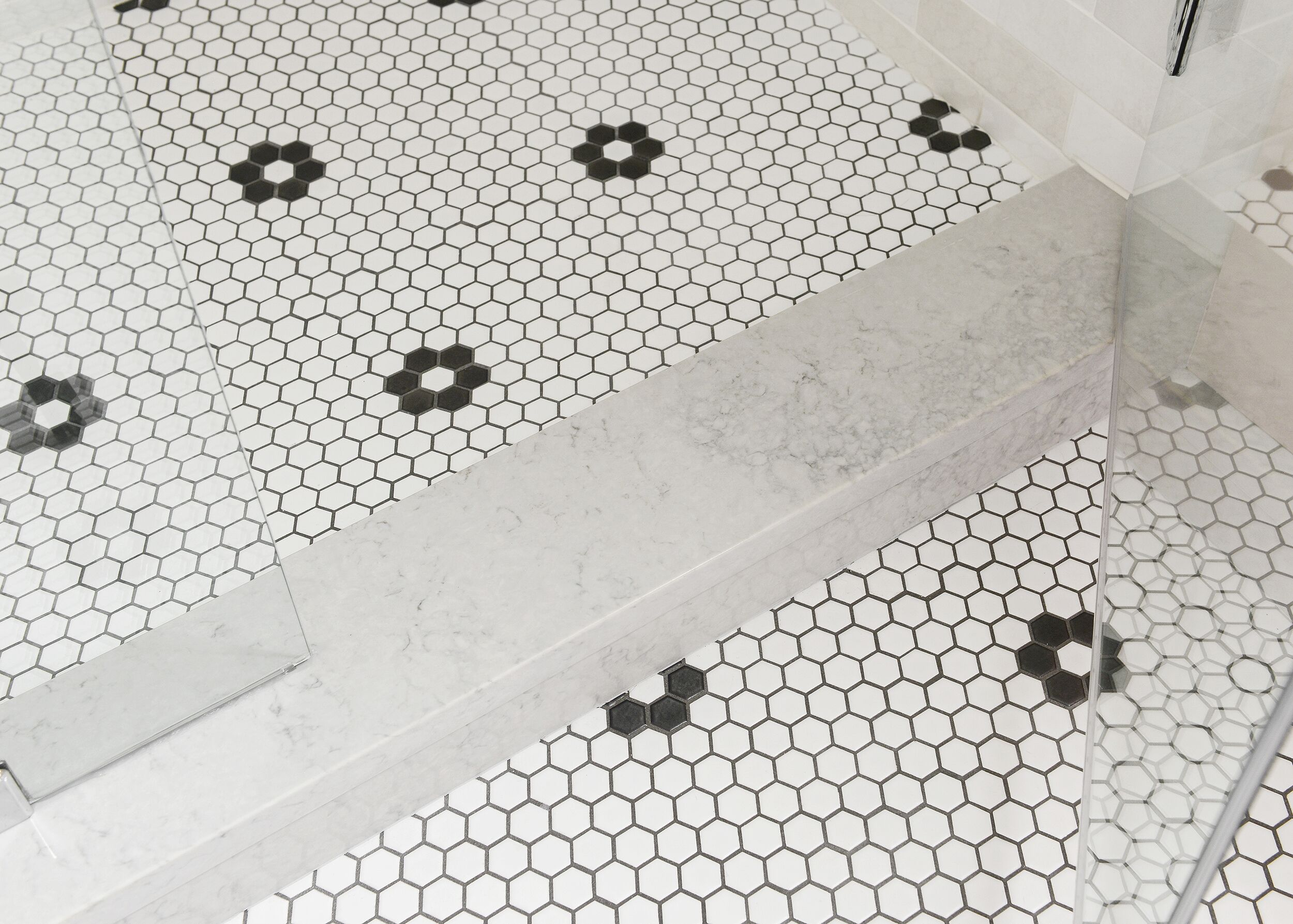 Shower floor with while round tiles and black accent