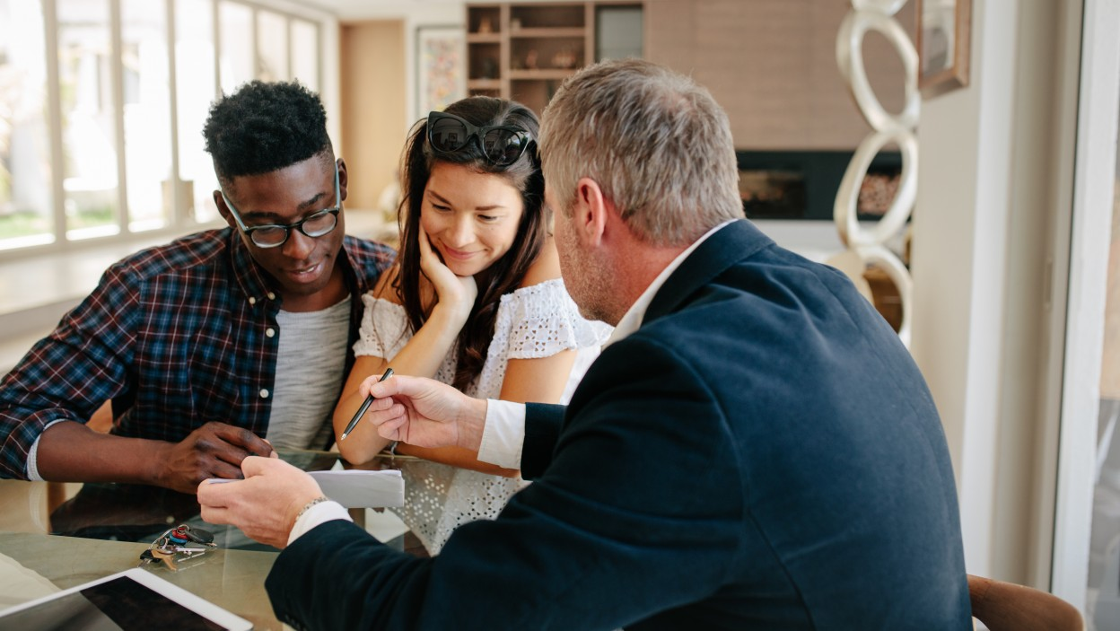 Real estate agent showing detail of lease agreement to interracial couple. Estate broker explaining lease agreement or purchase contract to couple in a new house.