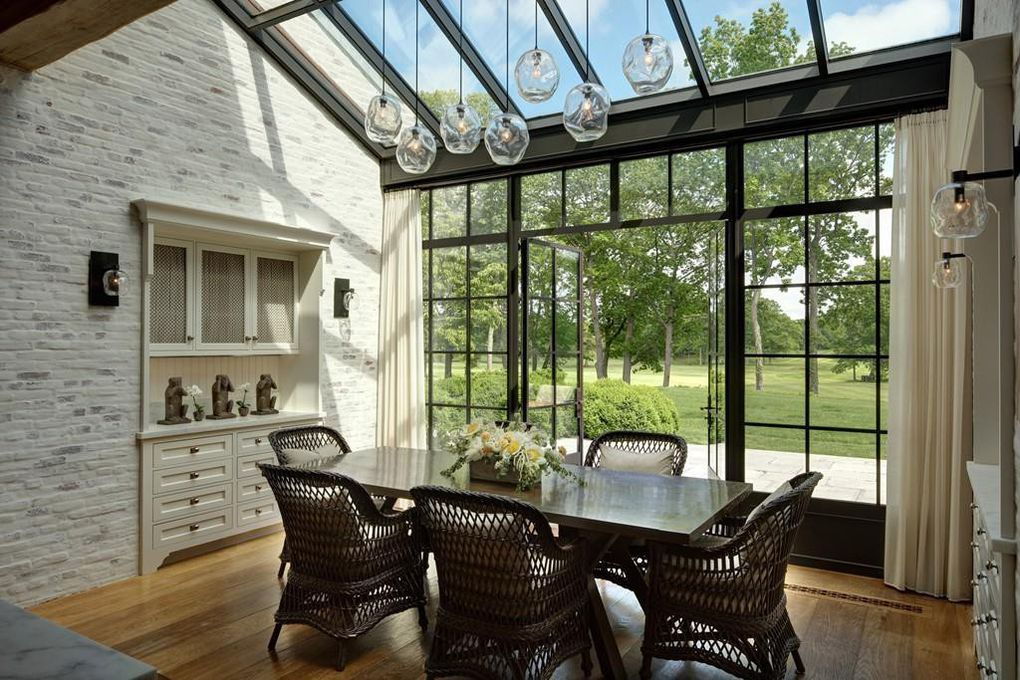 Tom Brady's home interior floor to ceiling windows and wooden ceiling beams add rustic vibes
