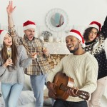 Happy New year. Multiethnic company dancing with champagne, black man playing Christmas song on acoustic guitar, copy space