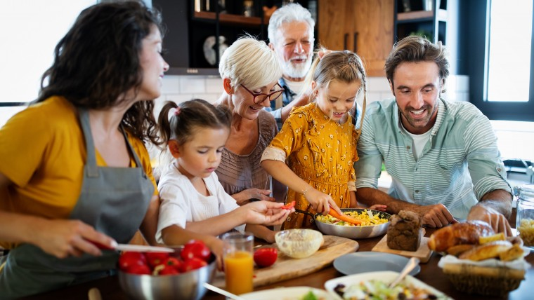 Cheerful happy family spending good time together while cooking in kitchen