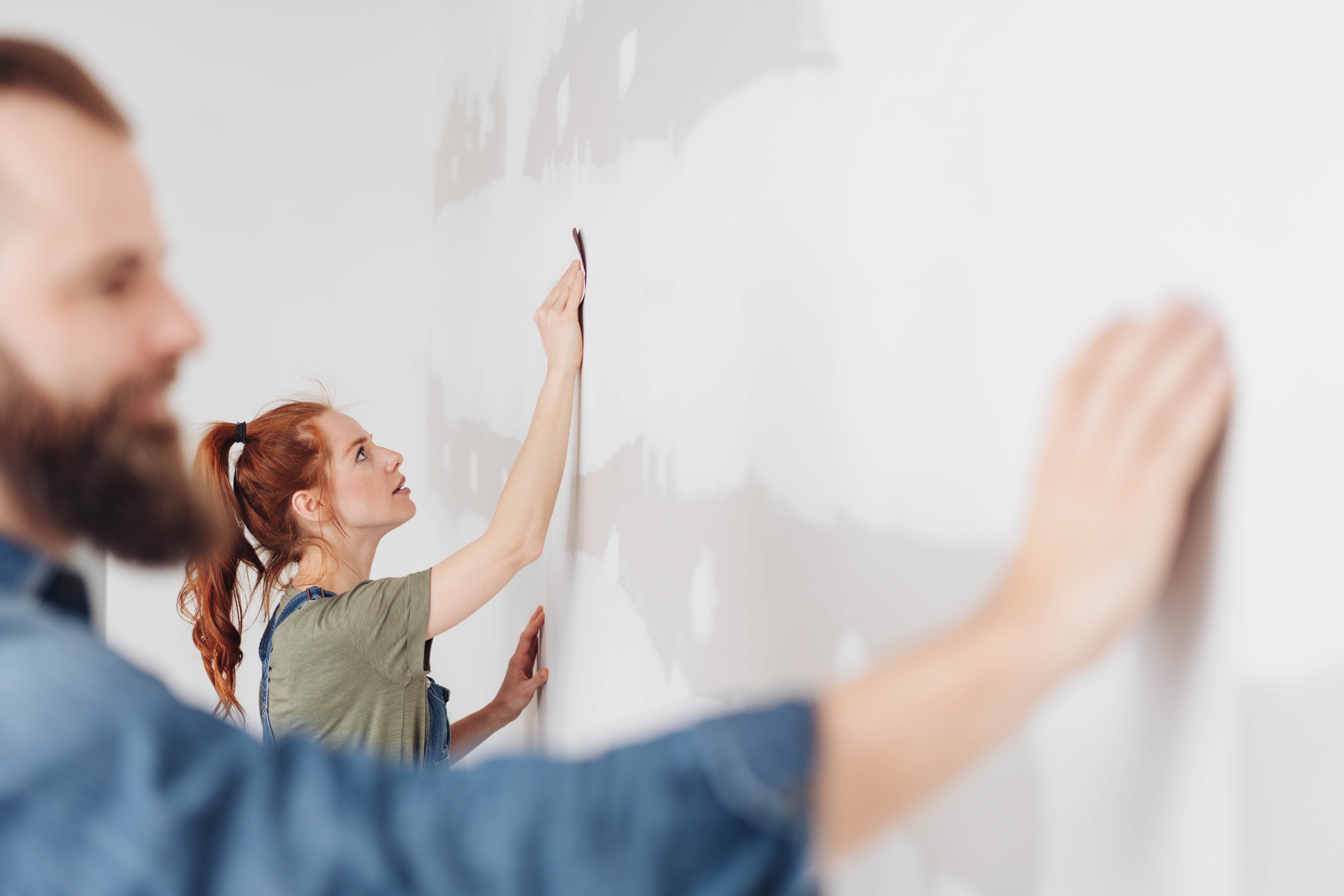 Young woman sanding an unpainted clad wall during DIY home improvements in a view past her husband in the foreground