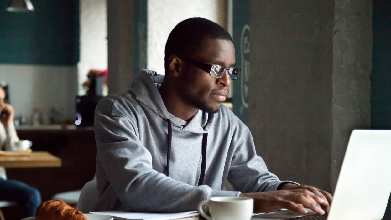 Serious millennial man using laptop sitting at cafe table, focused black casual guy communicating online, writing emails, distantly working or studying on computer in public place