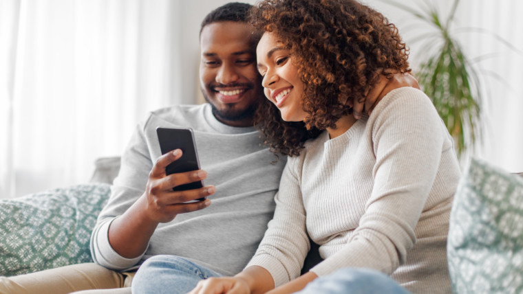 technology, internet and people concept - happy african american couple with smartphone at home