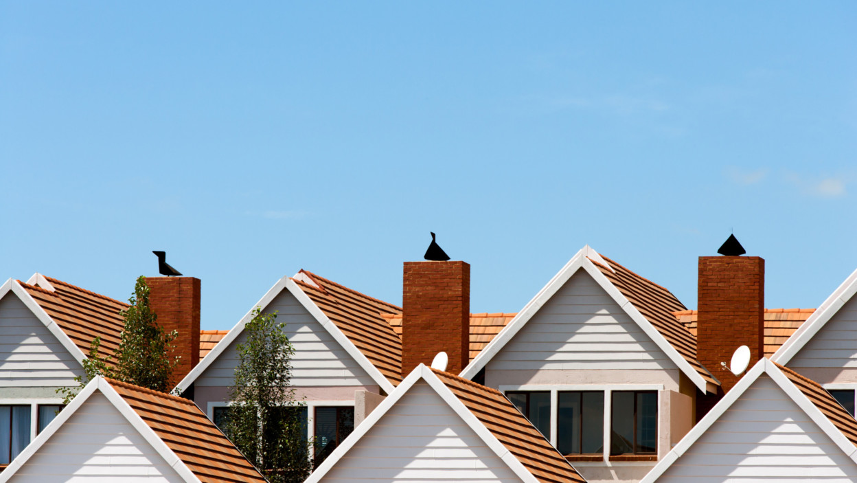 Close up detail of town house rooftops with chimneys against blue shy.