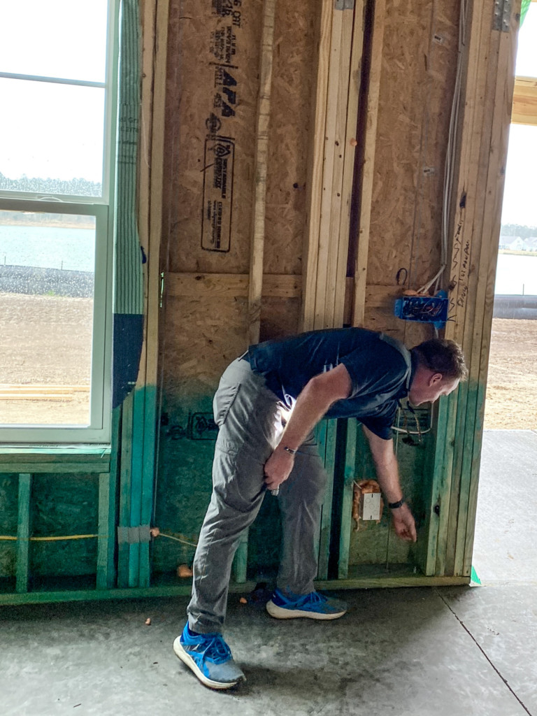 Man bending over pointing to the floor in partially constructed house.