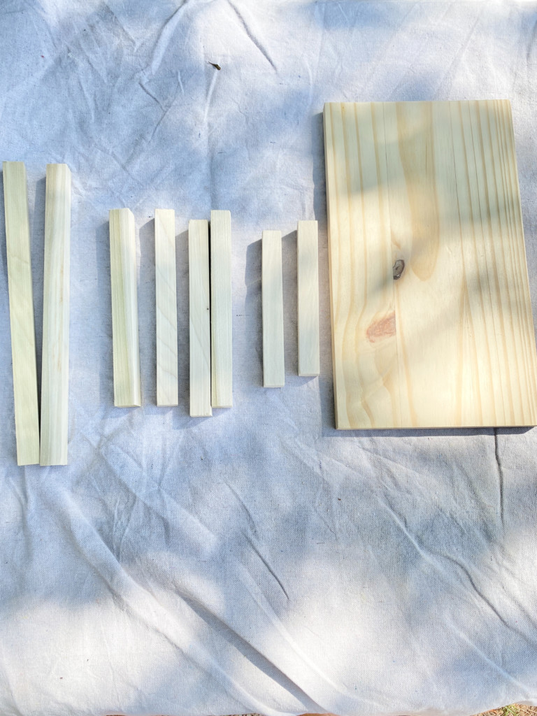 Square dowel pieces cut in various lengths next to a larger full size board all will be used for the scrap wood DIY outdoor lantern.