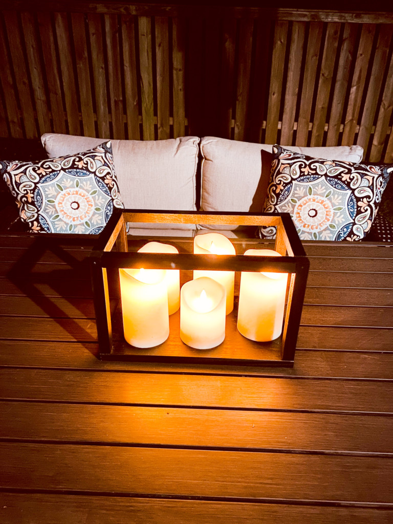 Scrap wood DIY outdoor lantern with 5 varying heights outdoor candles lit at night.