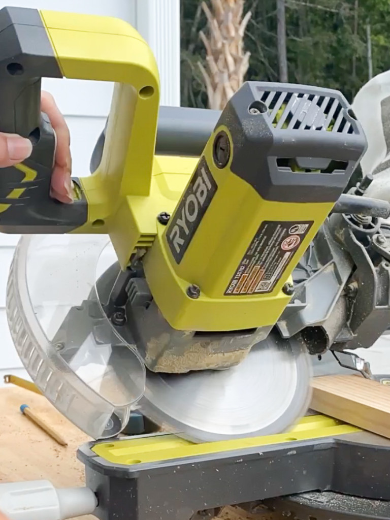 miter saw set at 45 degree angle leaning to left cutting into a piece of wood