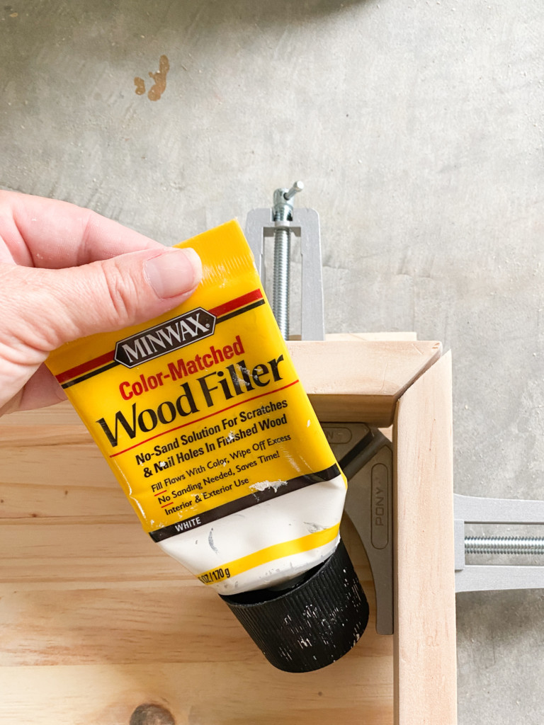 wood filler bottle being held in front of a gap between two wood pieces.