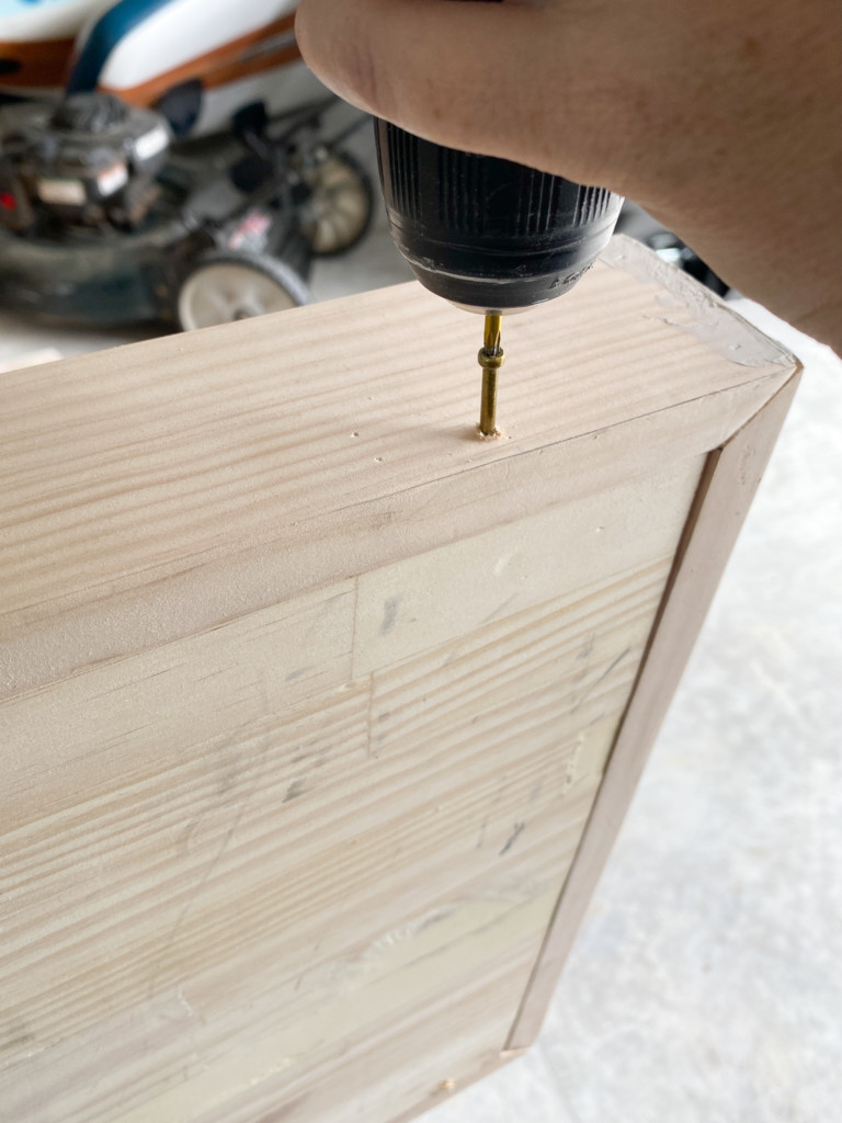 wood screw being placed on the side of the frame.